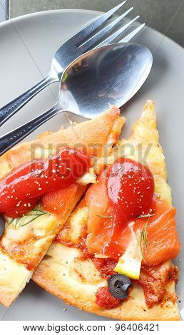Salmon Pizza and cutlery for eating.