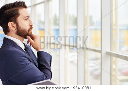 Pensive businessman looking in window