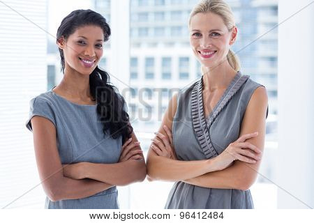 Side to side businesswomen looking at the camera in the office