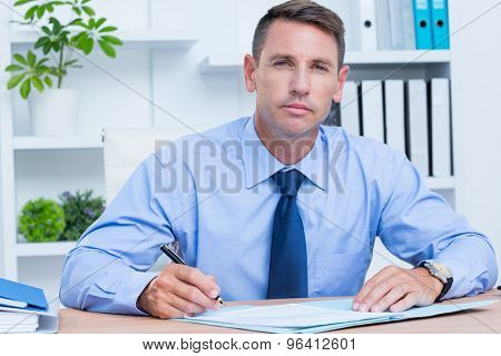 portrait of serious businessman writing in the office