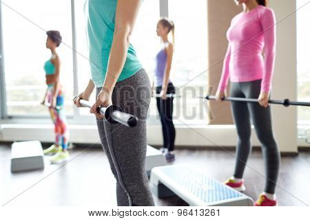 fitness, sport, people and lifestyle concept - close up of women exercising with bars and step platforms in gym