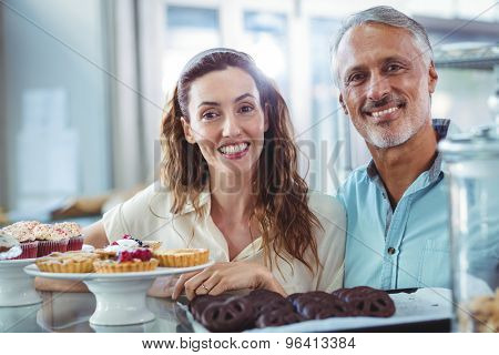 Cute couple looking at camera in the bakery store