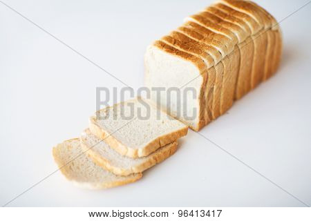 food, junk-food and unhealthy eating concept - close up of white sliced toast bread on table