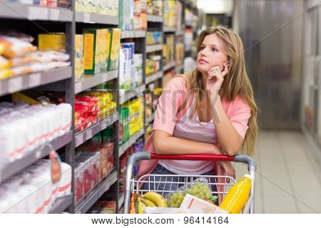 Pretty blonde woman looking at shelf in supermarket