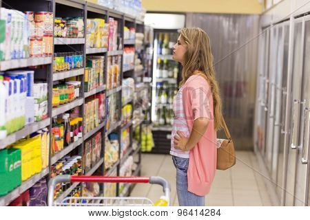 Pretty blonde woman buying a products in supermarket
