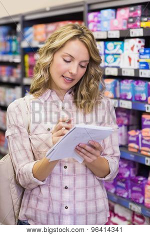 Smiling pretty blonde woman writing on her notepad in supermarket