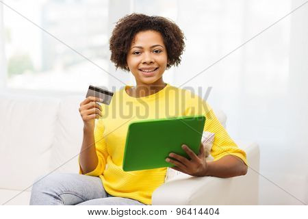 people, internet bank, online shopping, technology and e-money concept - happy african american young woman sitting on sofa with tablet pc computer and credit card at home