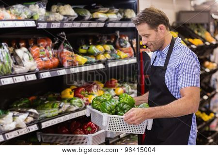 Smiling handsome worker holding a box with vegetable in supermarket