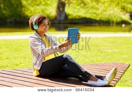 technology, lifestyle and people concept - smiling african american young woman or teenage girl with tablet pc computer and headphones listening to music or watching video in summer park