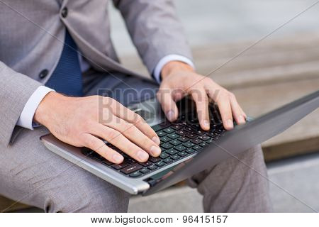 business, technology and people concept - close up of man with laptop computer sitting on bench in city