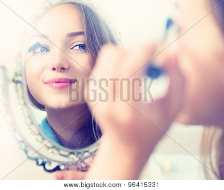 Beauty model girl looking in the mirror and applying mascara make up. Beautiful young woman apply makeup