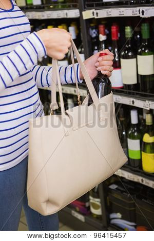 Woman putting a bottle of red wine on her bag at supermarket