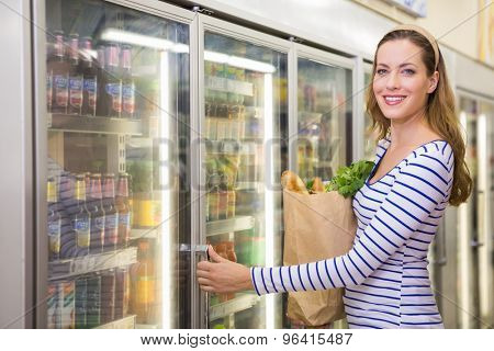 Pretty woman taking product on fridge at supermarket