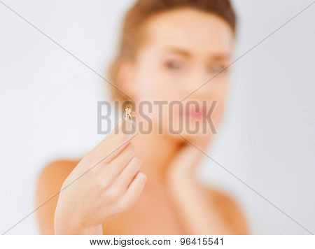 wedding, bridal, jewellery and luxury concept - beautiful woman looking at wedding ring and thinking