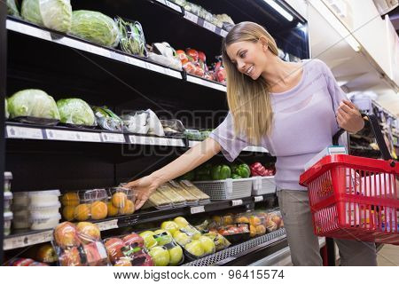 Smiling woman taking a vegetables in the aisle at the supermarket
