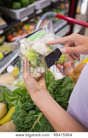 Over shoulder view of woman hands pointing at broccolis