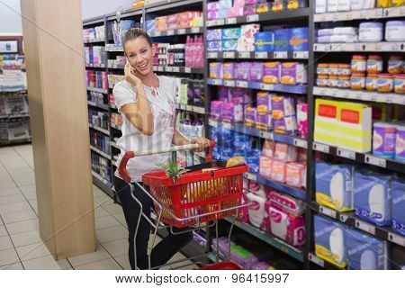 Woman buy products and calling at supermarket