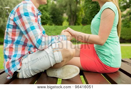 love, affection, feelings and people concept - close up of happy couple holding hands in park