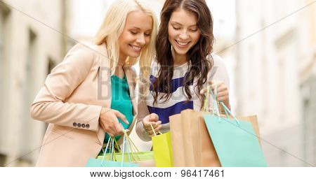 sale, shopping, tourism and happy people concept - two beautiful women looking inside shopping bags in the ctiy