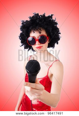 Pop star with mic in red dress against gradient