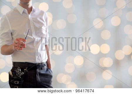 beauty and hair salon, hairstyle and people concept - close up of male stylist with scissors over blank holidays lights background