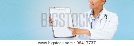 health care, people and medical concept - close up of smiling african american female doctor pointing finger to blank paper sheet on clipboard over blue background