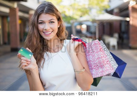Portrait of smiling woman with shopping bags and credit card looking at camera at the shopping mall