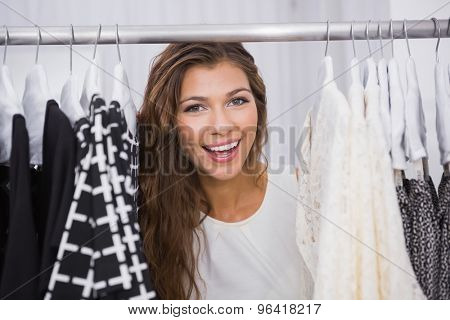 Portrait of smiling woman standing in-between clothes at a boutique