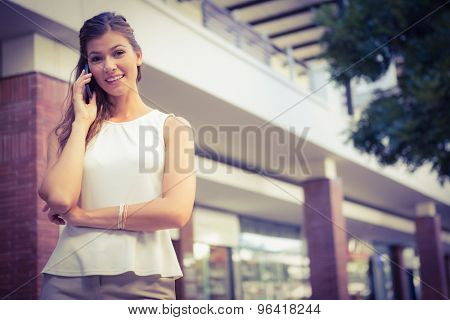 Portrait of smiling woman calling with smartphone and looking at camera at the shopping mall