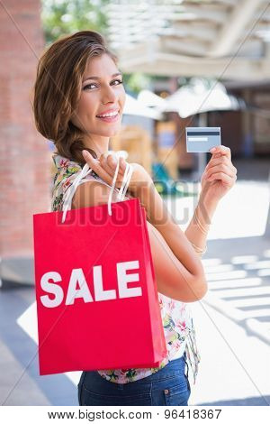 Portrait of smiling woman with sale shopping bag showing credit card at the shopping mall