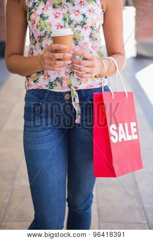 Woman walking with coffee to go and shopping bag at the shopping mall