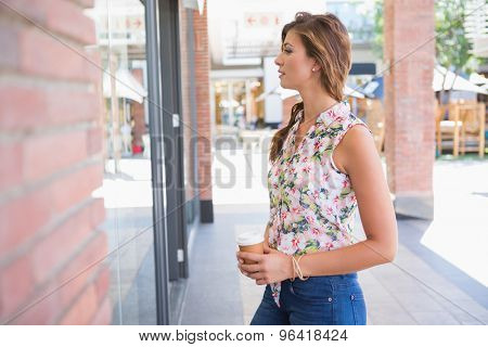 Woman with coffee to go looking at the window at the shopping mall