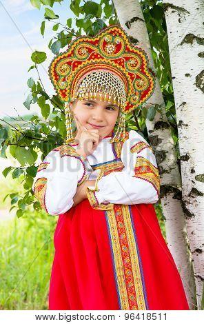Little Girl In Russian National A Sundress And A Kokoshnik Stand Near A Birch In Summer Day
