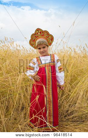 Little Girl In Russian National A Sundress And A Kokoshnik Stand In A Wheat Field In Summer Day