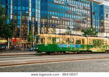 Tram departs from a stop on street Aleksanterinkatu in Helsinki