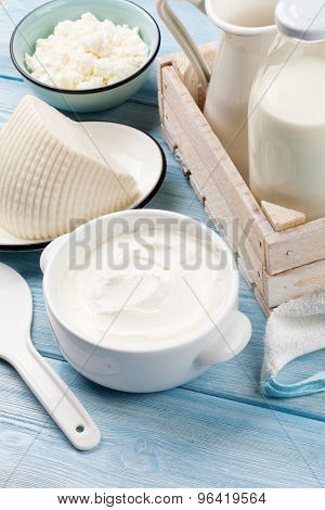 Dairy products on wooden table. Sour cream, milk, cheese and yogurt