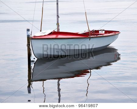 Small Sailboat Moored At Sea