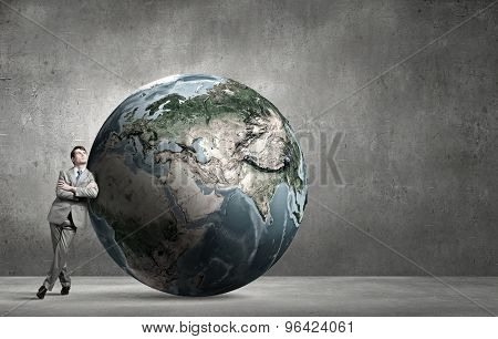 Businessman leaning on huge Earth planet. Elements of this image are furnished by NASA