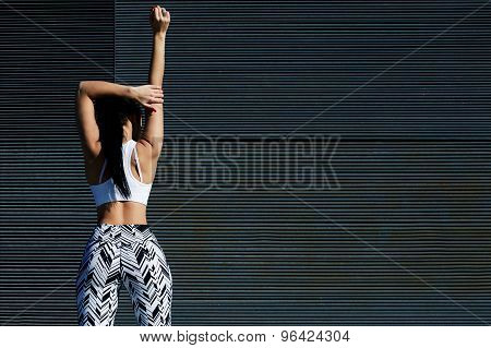 Cropped back view portrait of sporty woman with perfect figure and buttocks stretching her arms
