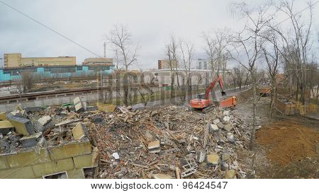 MOSCOW - APR 17, 2015: Excavator loads truck by old building remains at spring cloudy day. Aerial view