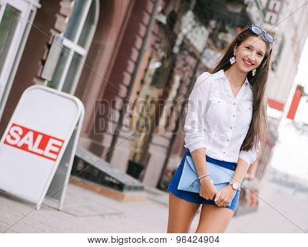 Young woman in the city over shops