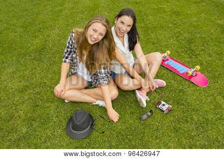 Female best friends sitting on the grass and having a good time