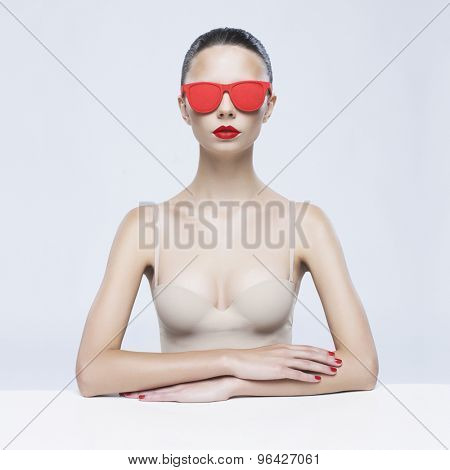 Fashion studio photo of young elegant lady in red sunglasses