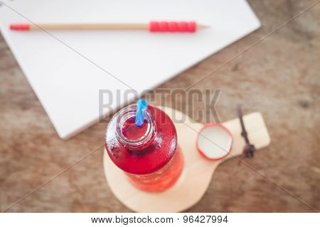 Red Syrup In The Bottle On Wooden Plate
