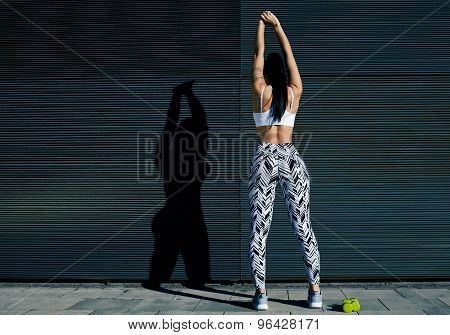 Back view portrait of young woman with perfect figure stretching her hands against black wall