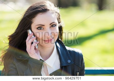 Portrait of a smiling young woman using a mobile phone. Some controlled flare in the foreground