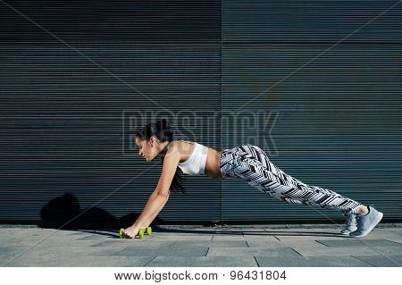 Female in workout gear doing push-ups with some weights against wall with copy space for your text