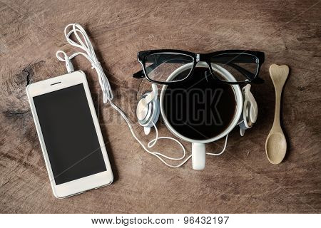 Cup Of Coffee With Earphone And Cellphone On Wooden Background
