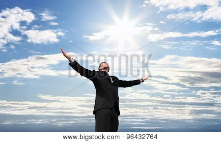 business man on top of success open arms to the sky