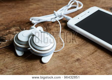 Earphone With Smartphone On Wooden Table